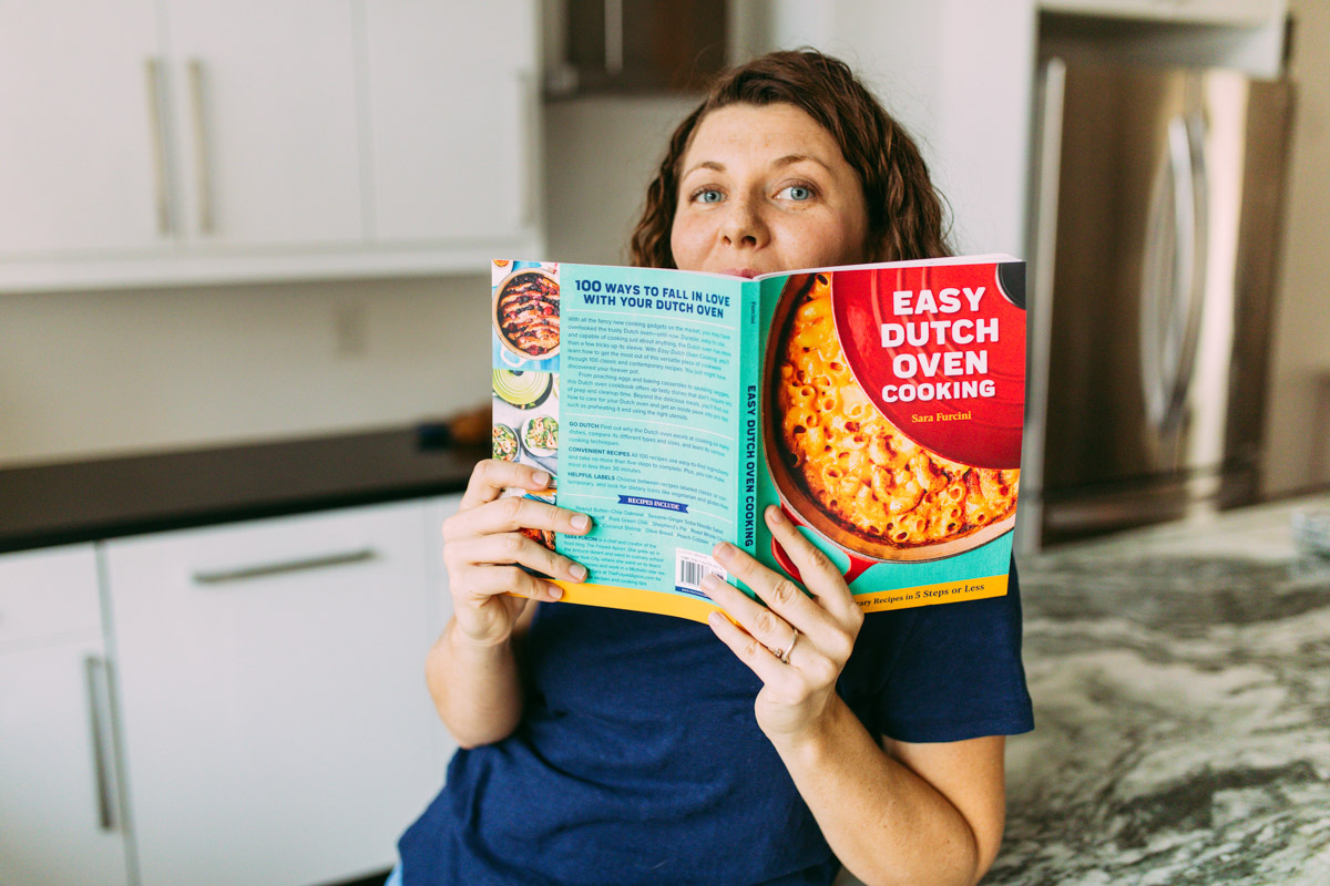 chef Sara Furcini holding Easy Dutch Oven Cooking cookbook