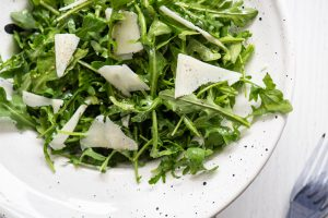 arugula salad in a white bowl with shaved Pecorino Romano on top