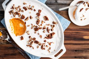 sweet potato casserole with coconut whipped cream on top and maple candied pecans as garnish